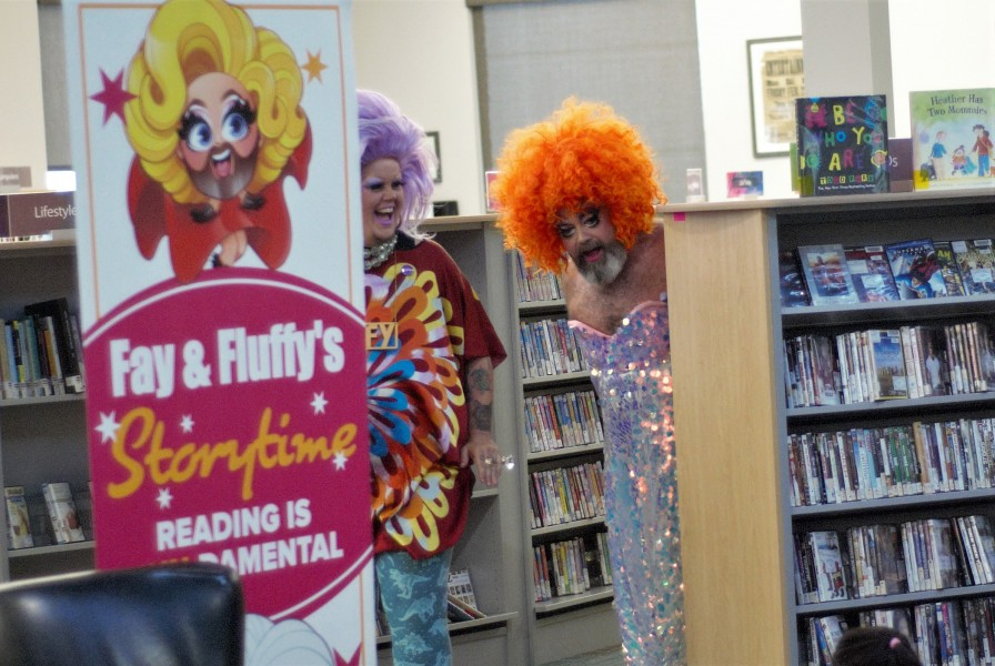 Fluffy and Fay peak out of the shelves before making their entrance Saturday at the NOTL Public Library. (Brittany Carter/Niagara Now)