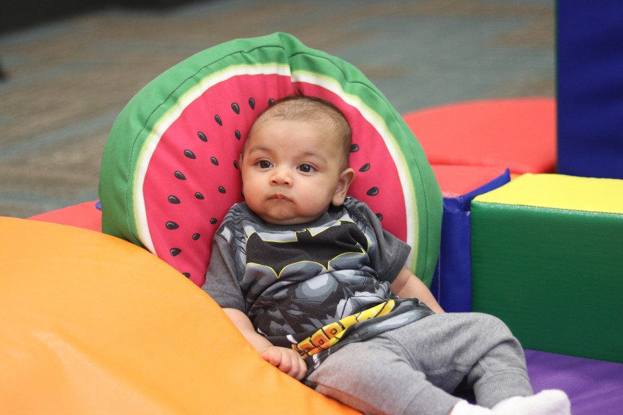 Kiaan Moledina, who's only 12 weeks, watches other toddlers play.