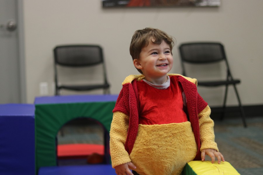 Maverick Pepe, dressed as Winnie-the-Pooh, plays during Tumble Tots program at the library.