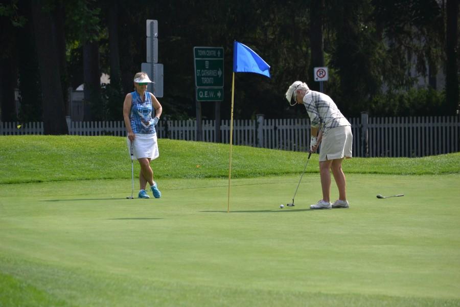 Ginny Green, who won the women's A flight, putts on #17. Yolanda Henry looks on. (Kevin MacLean/Niagara Now)